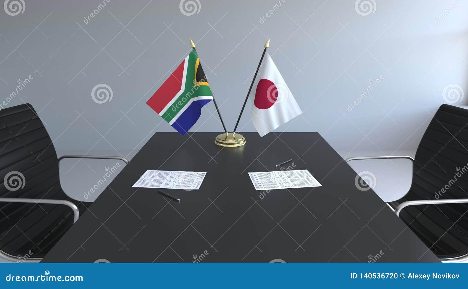 Флаги Южной Африки и Японии и бумаги на таблице Переговоры и подписание международного соглашения схематическо