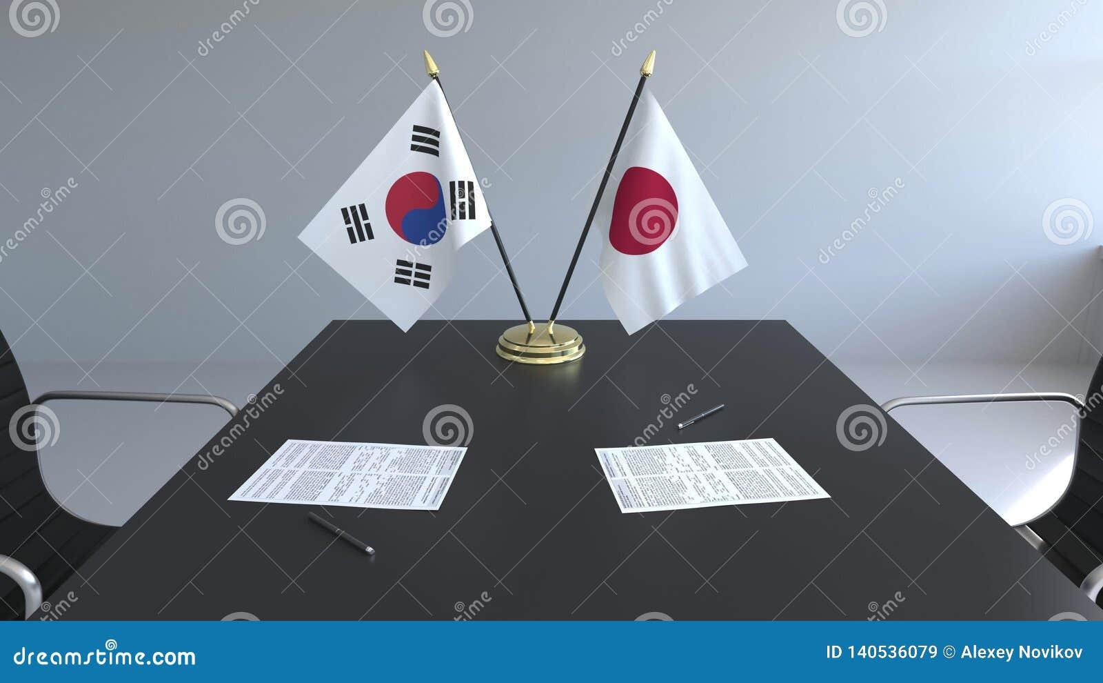 Флаги Южной Кореи и Японии и бумаги на таблице Переговоры и подписание международного соглашения схематическо