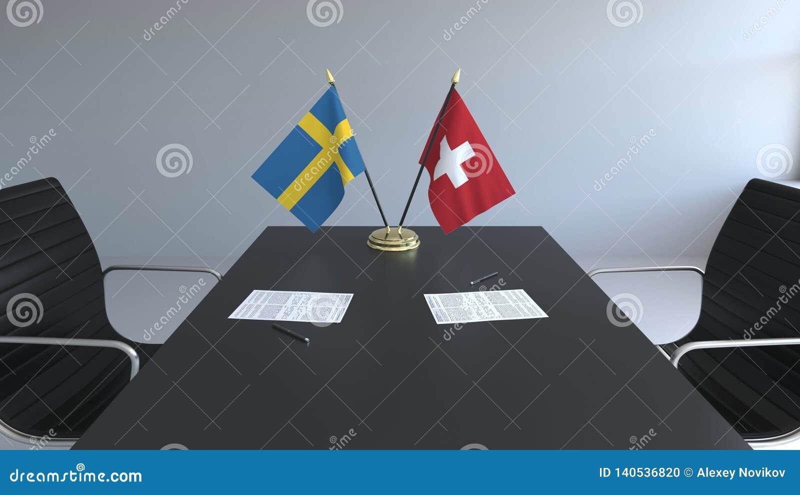 Флаги Швеции и Швейцарии и бумаги на таблице Переговоры и подписание международного соглашения схематическо