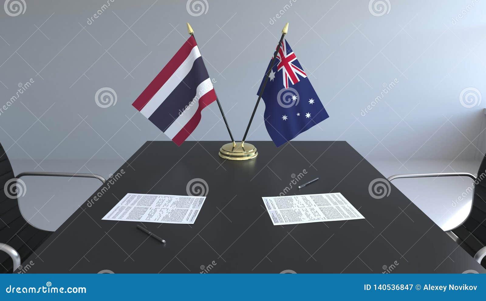 Флаги Таиланда и Австралии и бумаги на таблице Переговоры и подписание международного соглашения схематическо