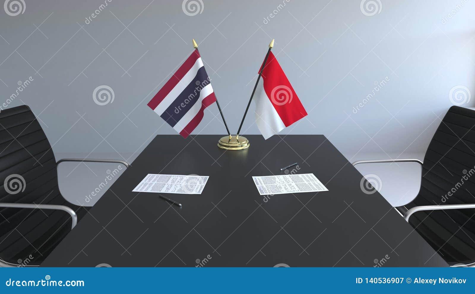 Флаги Таиланда и Индонезии и бумаги на таблице Переговоры и подписание международного соглашения схематическо