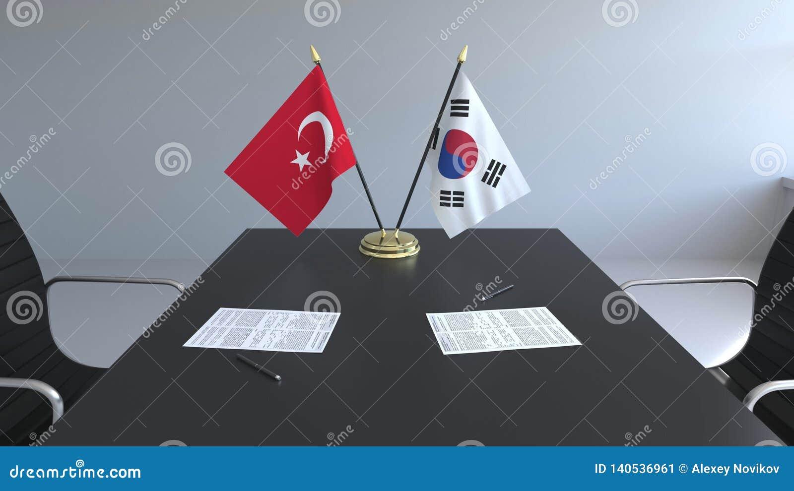 Флаги Турции и Южной Кореи и бумаги на таблице Переговоры и подписание международного соглашения схематическо