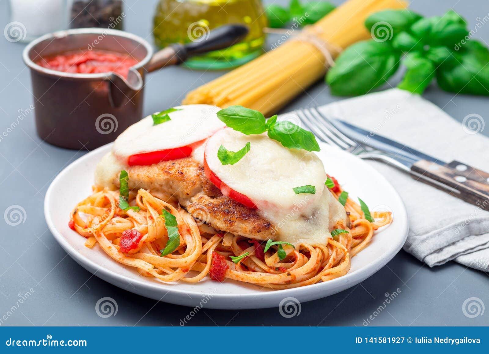 Цыпленок caprese с сыром томата и моццареллы, который служат с linguine, томатным соусом и базиликом, горизонтальными
