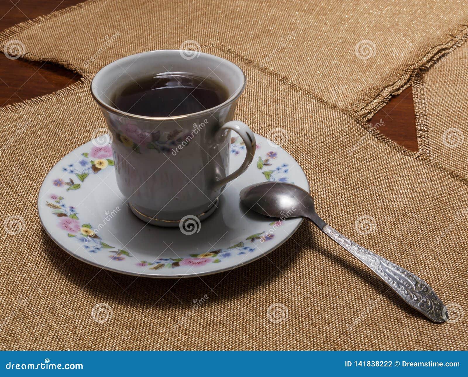 Чашка черного чая на поддоннике на таблице с салфетками