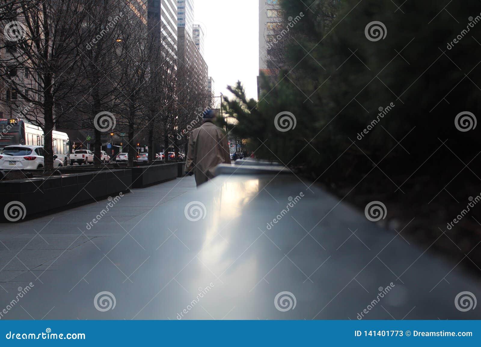 Человек идя на пальто зимы тротуара нося