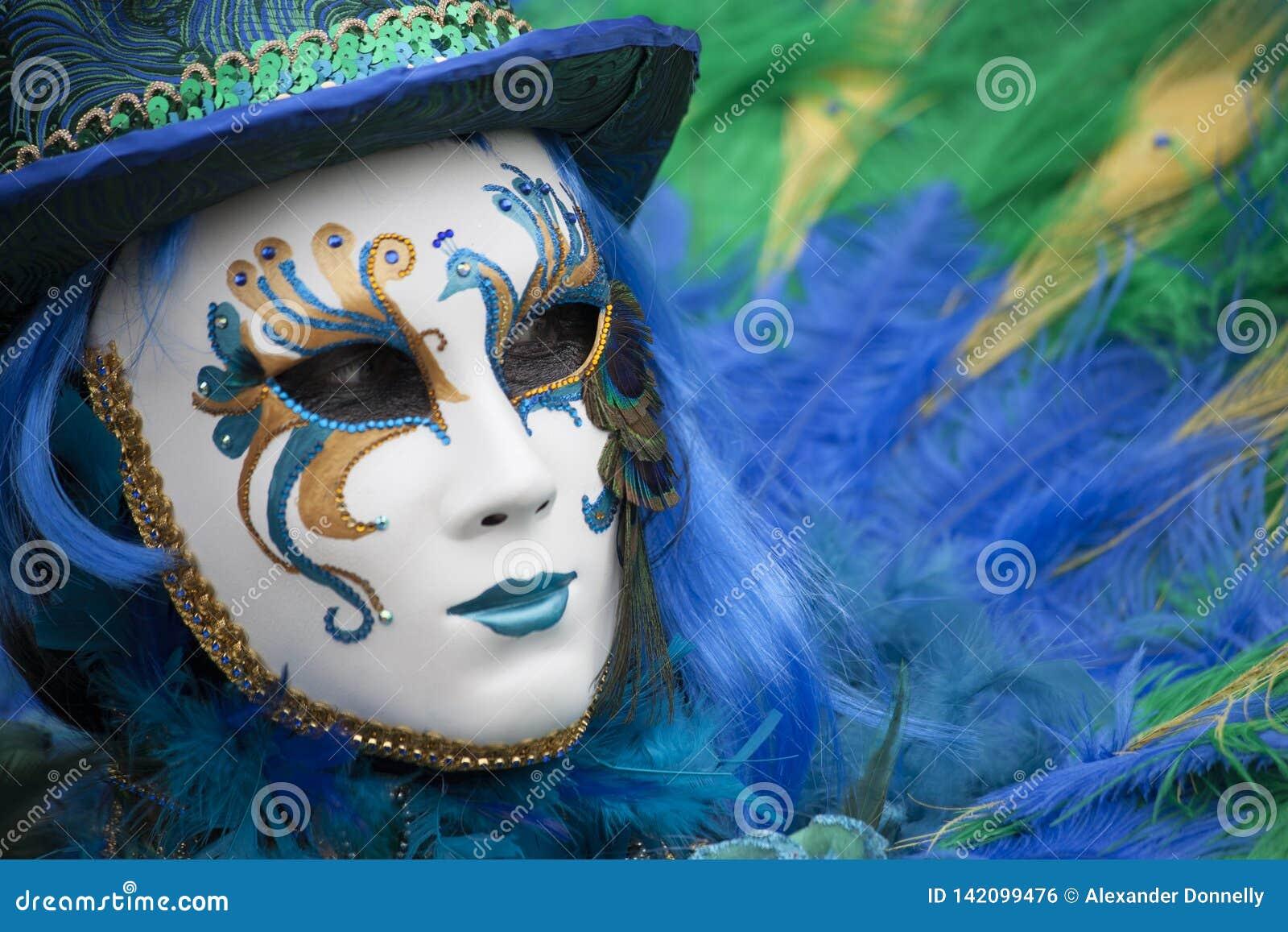 Человек на масленице Венеции одетый в голубом, желтом & зеленом венецианском костюме и венецианской маске с пером Венецией Италие
