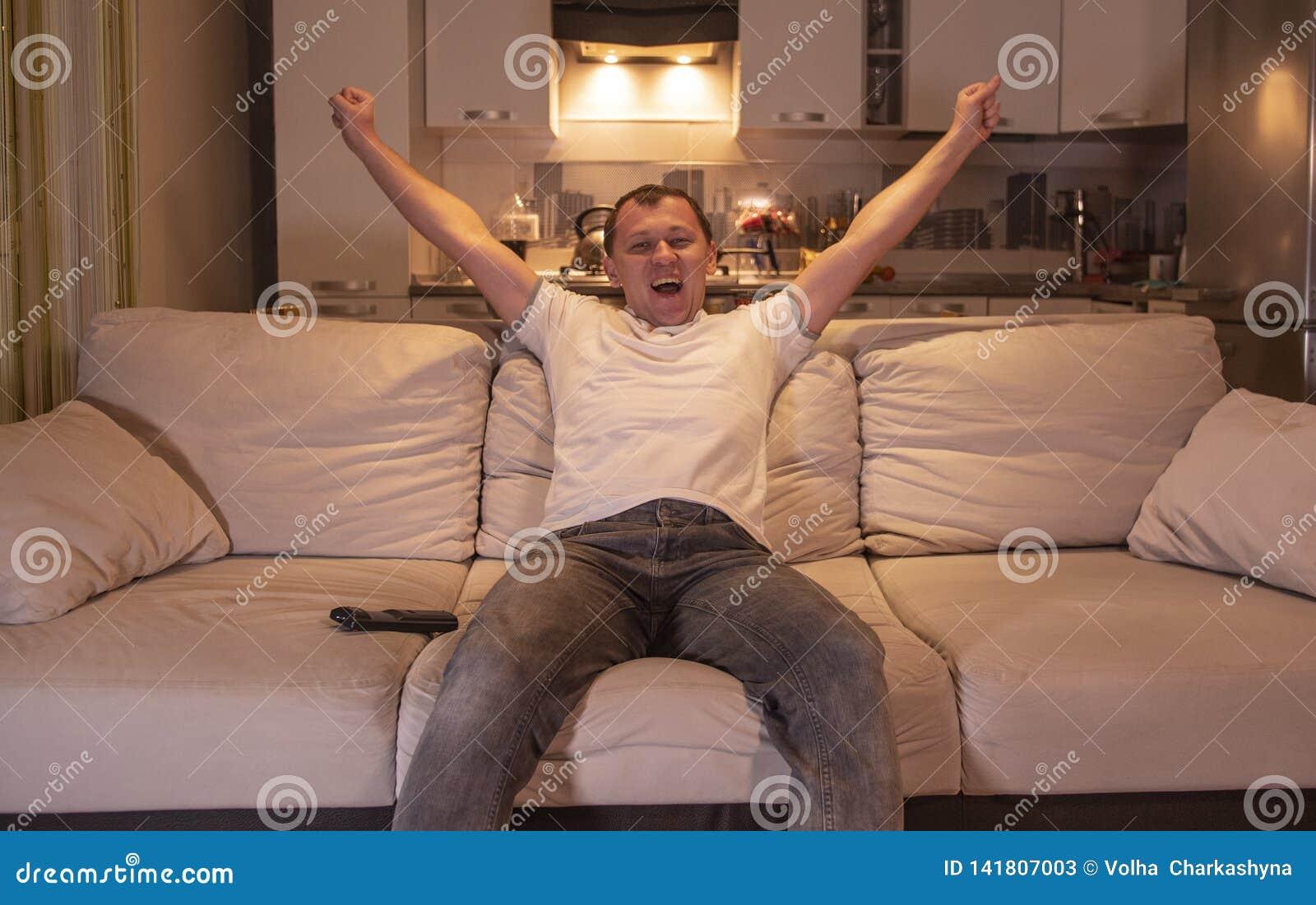 Человек смотря игру дома сидеть на софе в вечере по телевизору, поддерживает футбольную команду, радуется цель