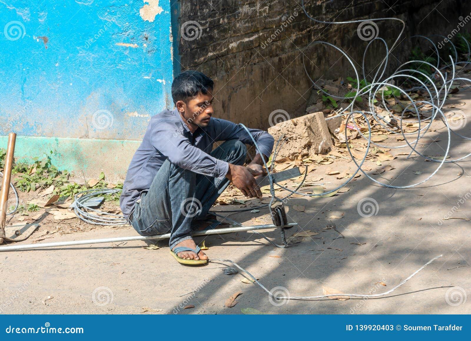 Человек работая с электрическими проводами без нося шестерней безопасности