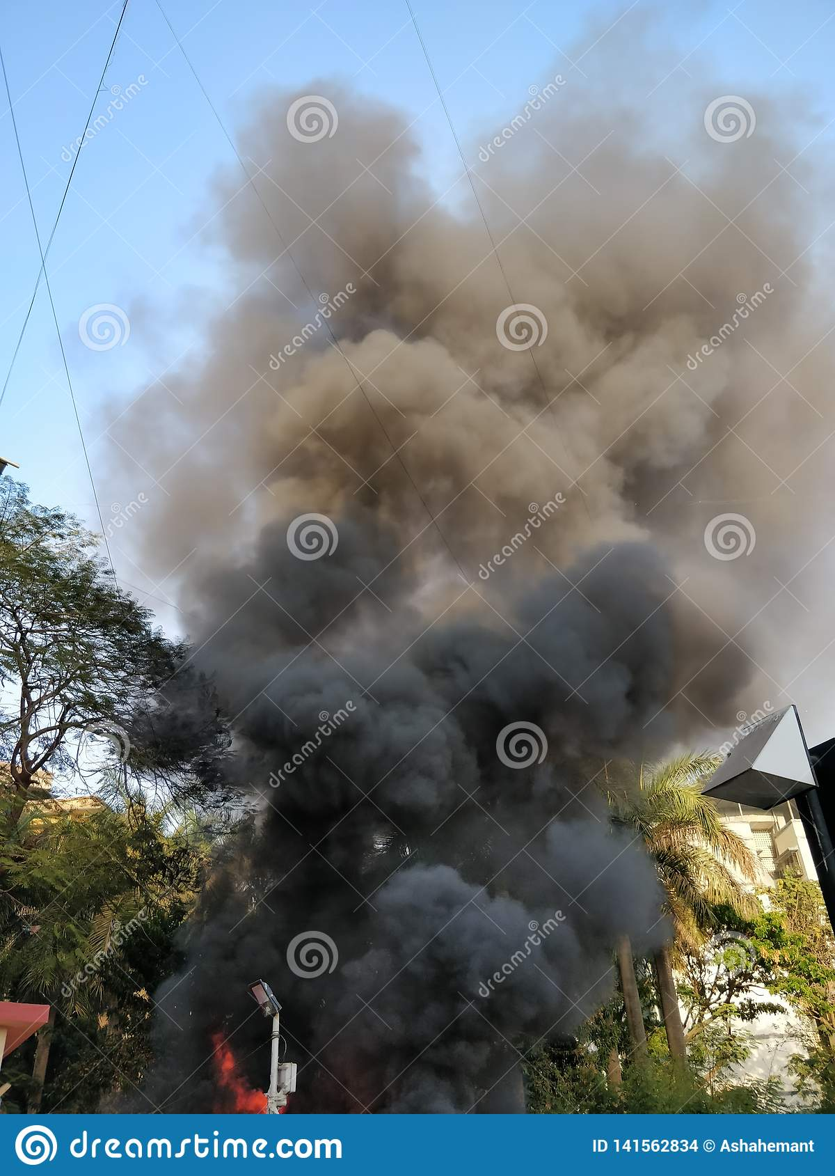 Черный дым приходя из здания горящего