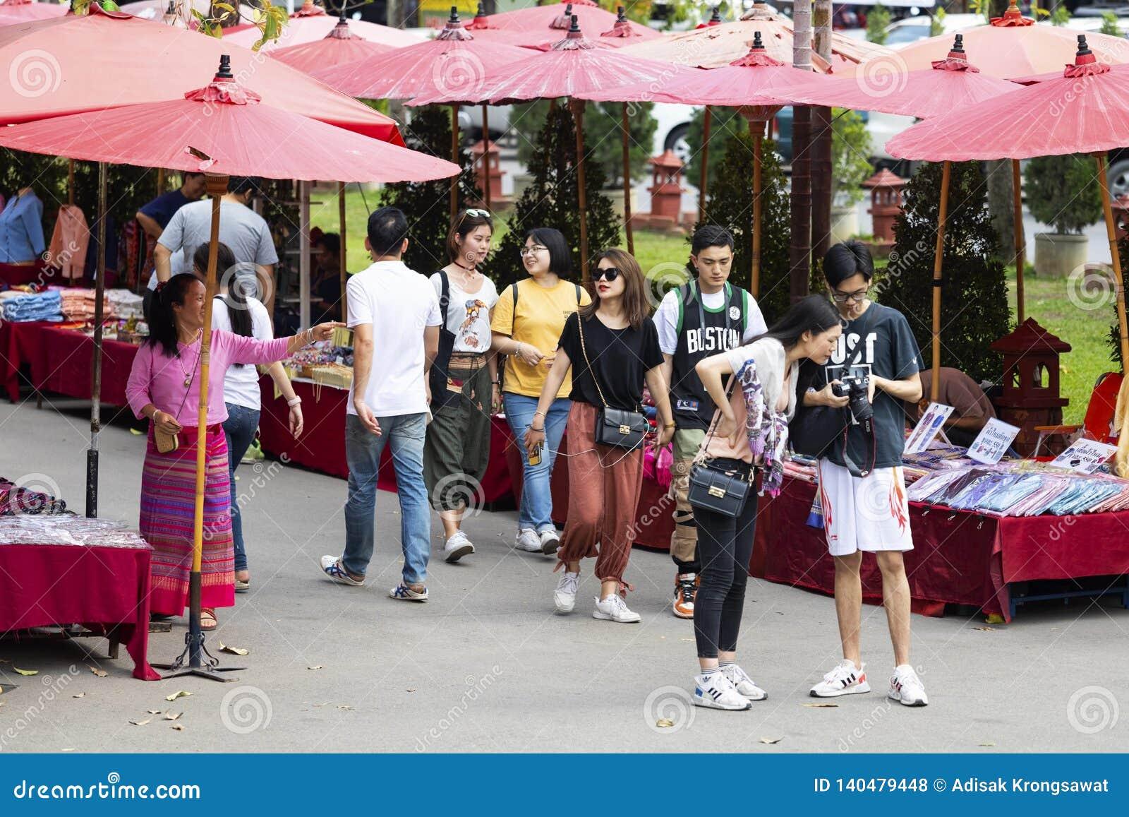 ЧИАНГМАЙ ТАИЛАНД - 17-ое февраля 2019: Уличный рынок воскресенья, в виске Wat Phra Singh Торговая операция местных туристов прихо