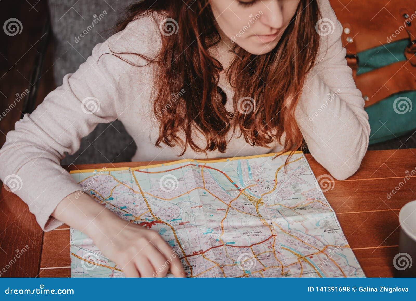 Чтение путешественника девушки молодой женщины красное главное смотря бумажную карту в кафе