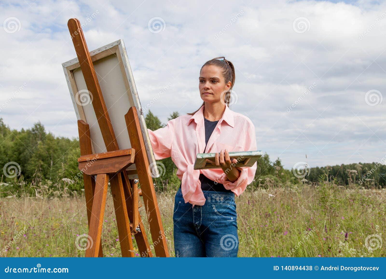 Художник красит изображение в поле