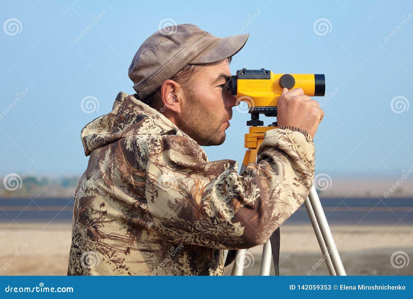 Работник с уровнем, построитель топографа с оборудованием геодезии близко к шоссе, с мобильным телефоном, усмехаясь