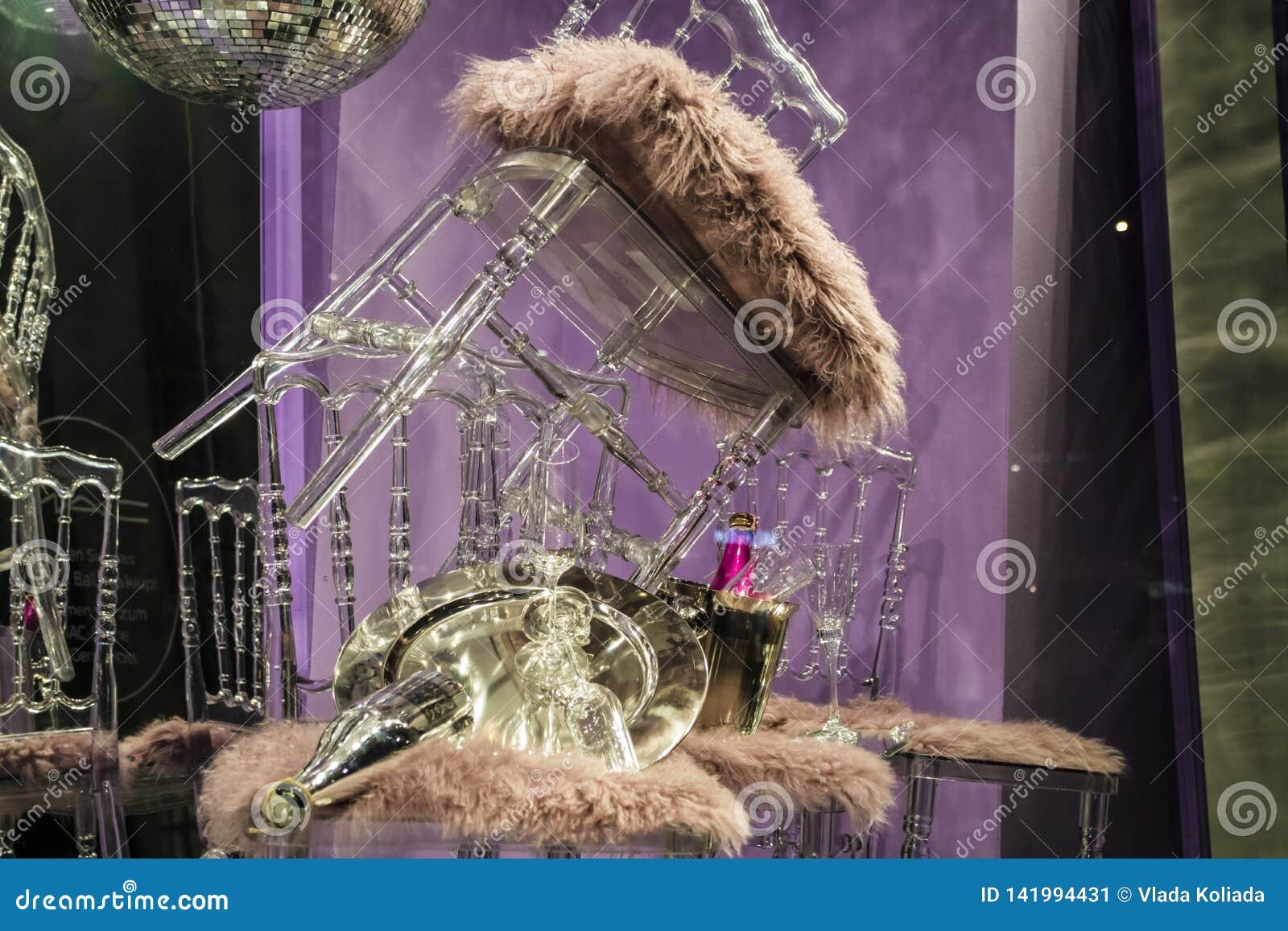 Разбросанные стулья и стекла, бутылки шампанского экспозиция Декоративное шоу-окно Розовые цветы Необыкновенное решение беспорядо