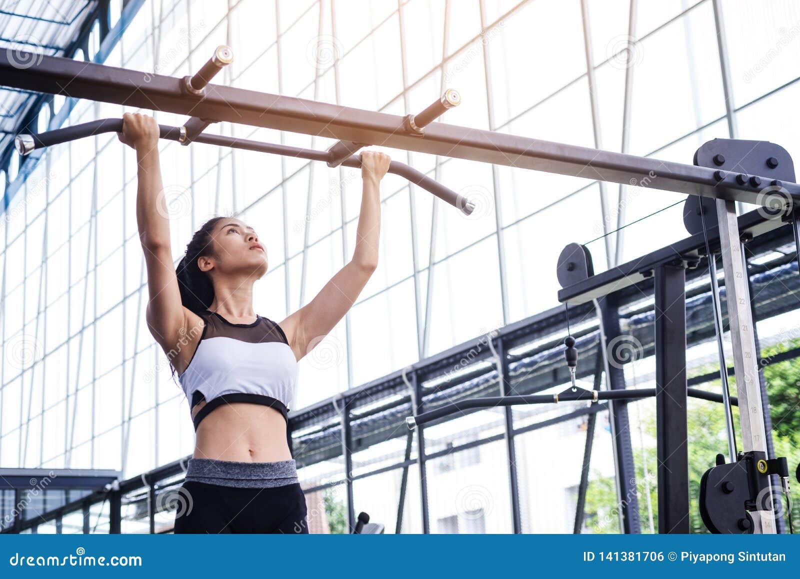 Разминка тренировки женщины фитнеса с тягой тренировк-машины вверх на баре в спортзале фитнес-центра уклад жизни принципиальной с