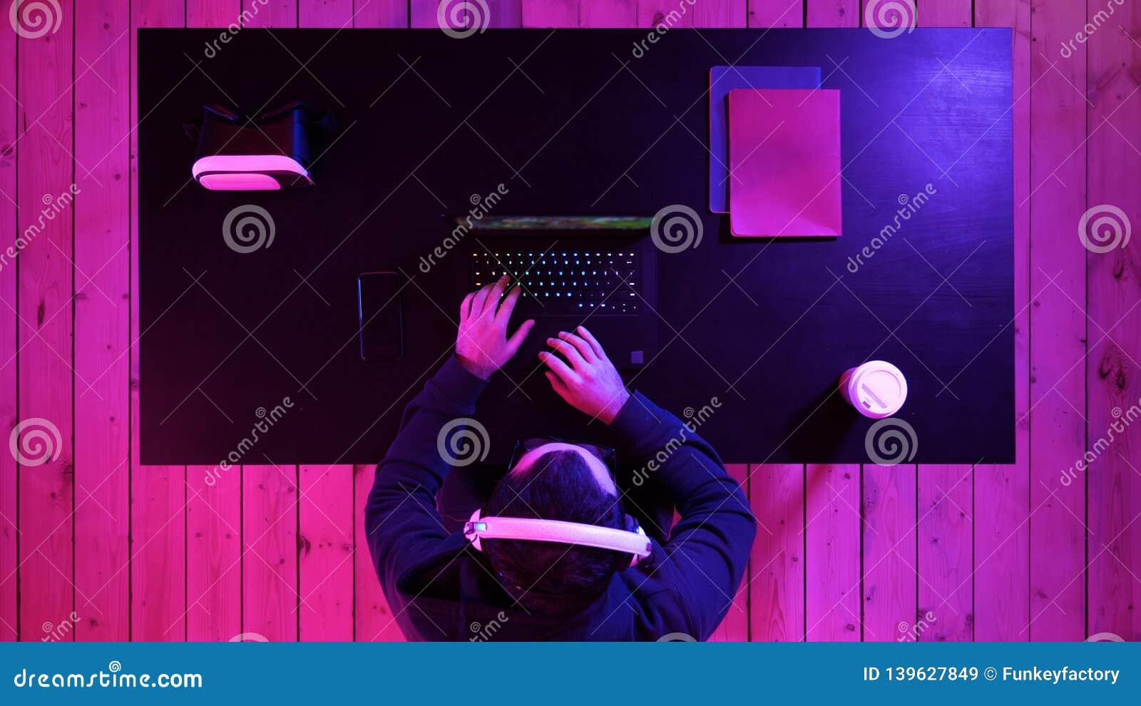 Радостный молодой gamer играя видеоигры дома на потоке компьютера идущем