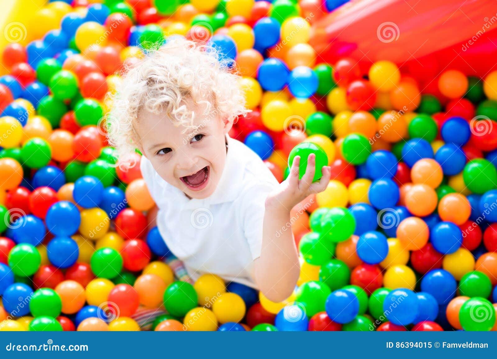 Ребенок играя в яме шарика на крытой спортивной площадке