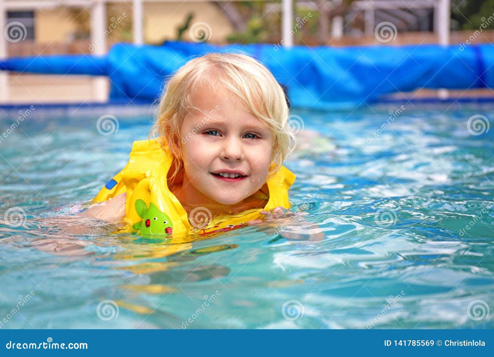 Ребенок малыша нося раздувной спасательный жилет уча поплавать в бассейне семьи задворк