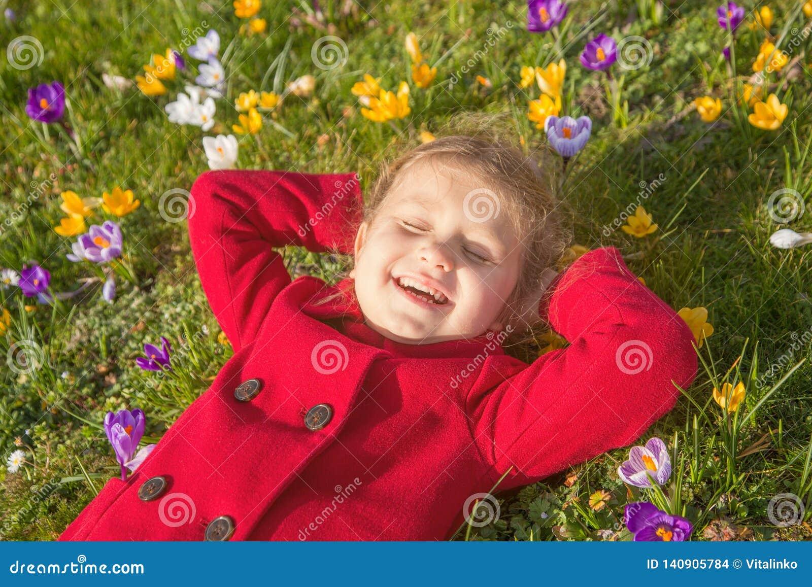 Ребенок наслаждается весной, солнцем и цветками Первые цветки и счастливые дети