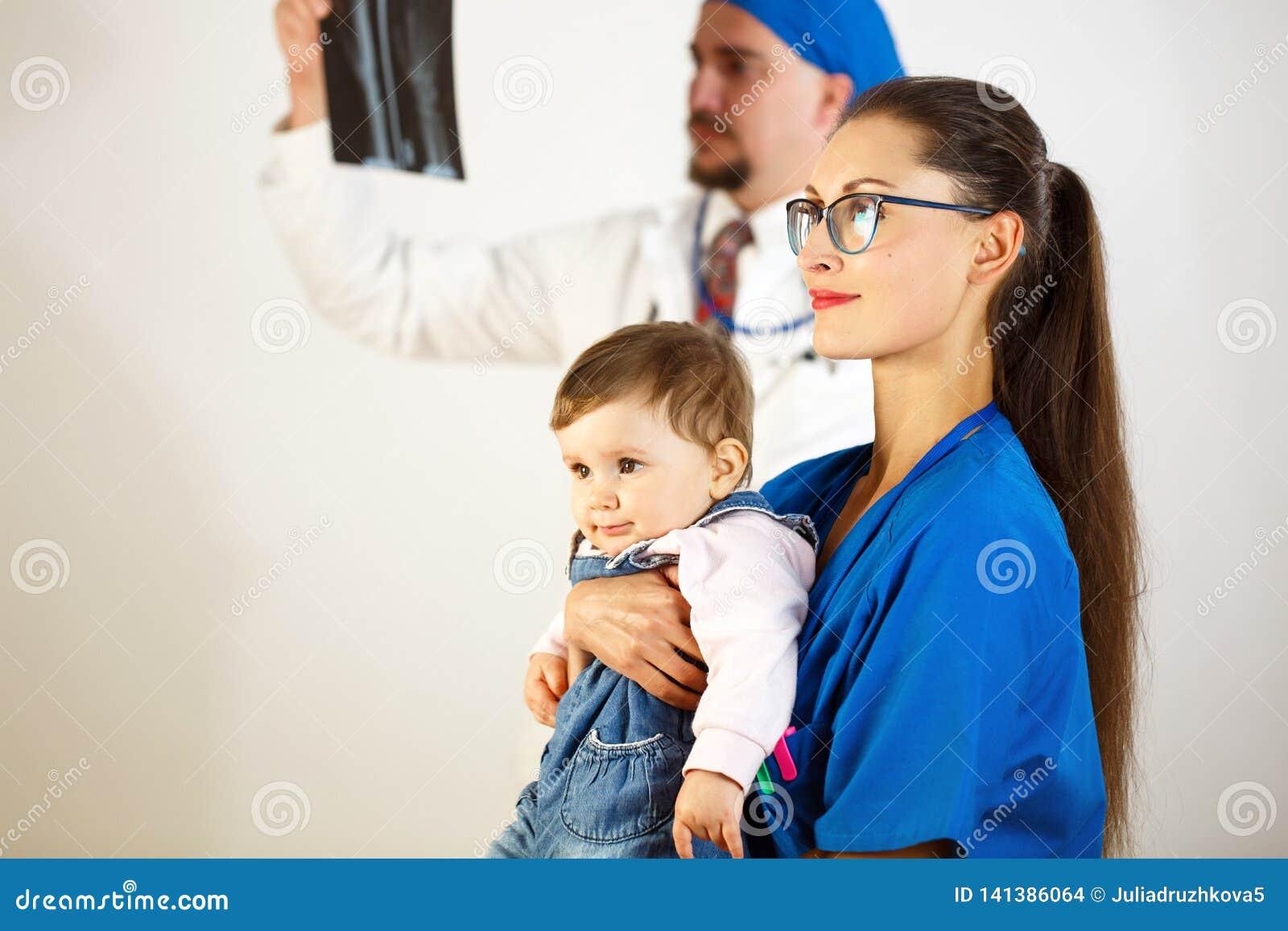 Ребенок сидит в руках доктора, второй доктор смотрит рентгеновский снимок Белая предпосылка