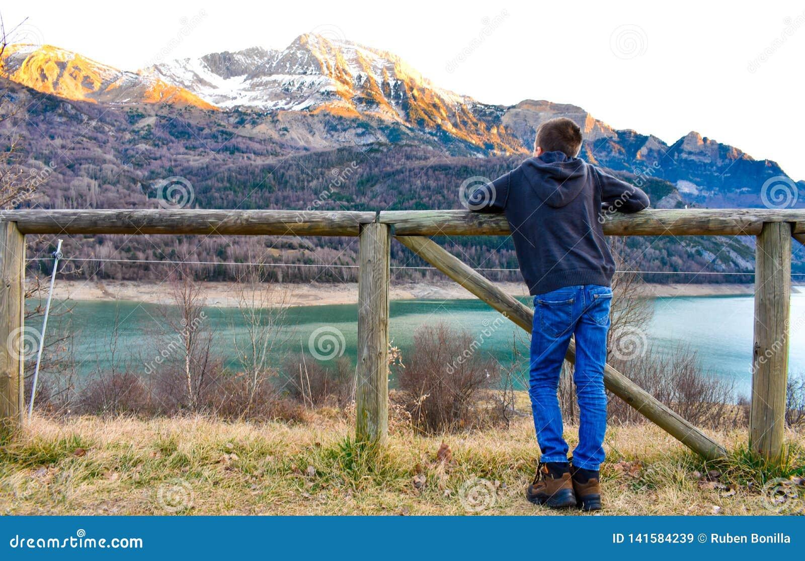 Ребенок с его оружиями на деревянной загородке наблюдающ снегом на пиках гор и открытого моря озера в