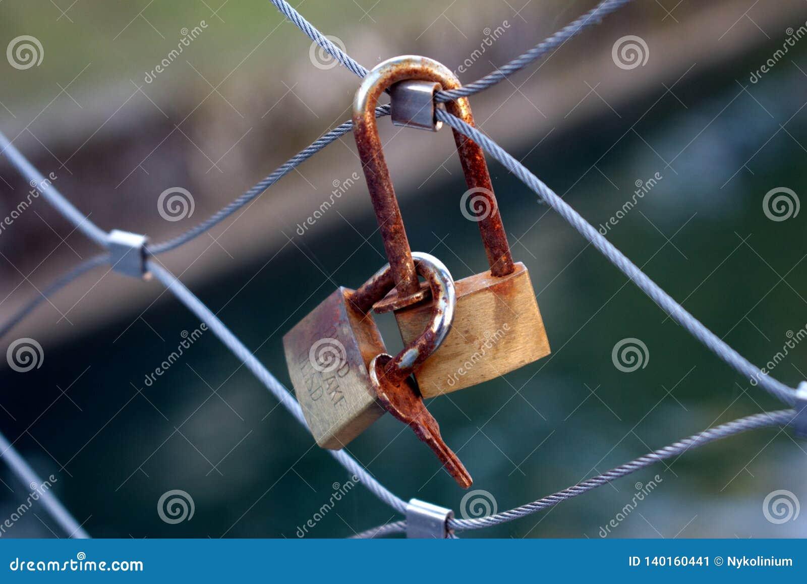 Ржавые ключи и замки на металлической загородке моста