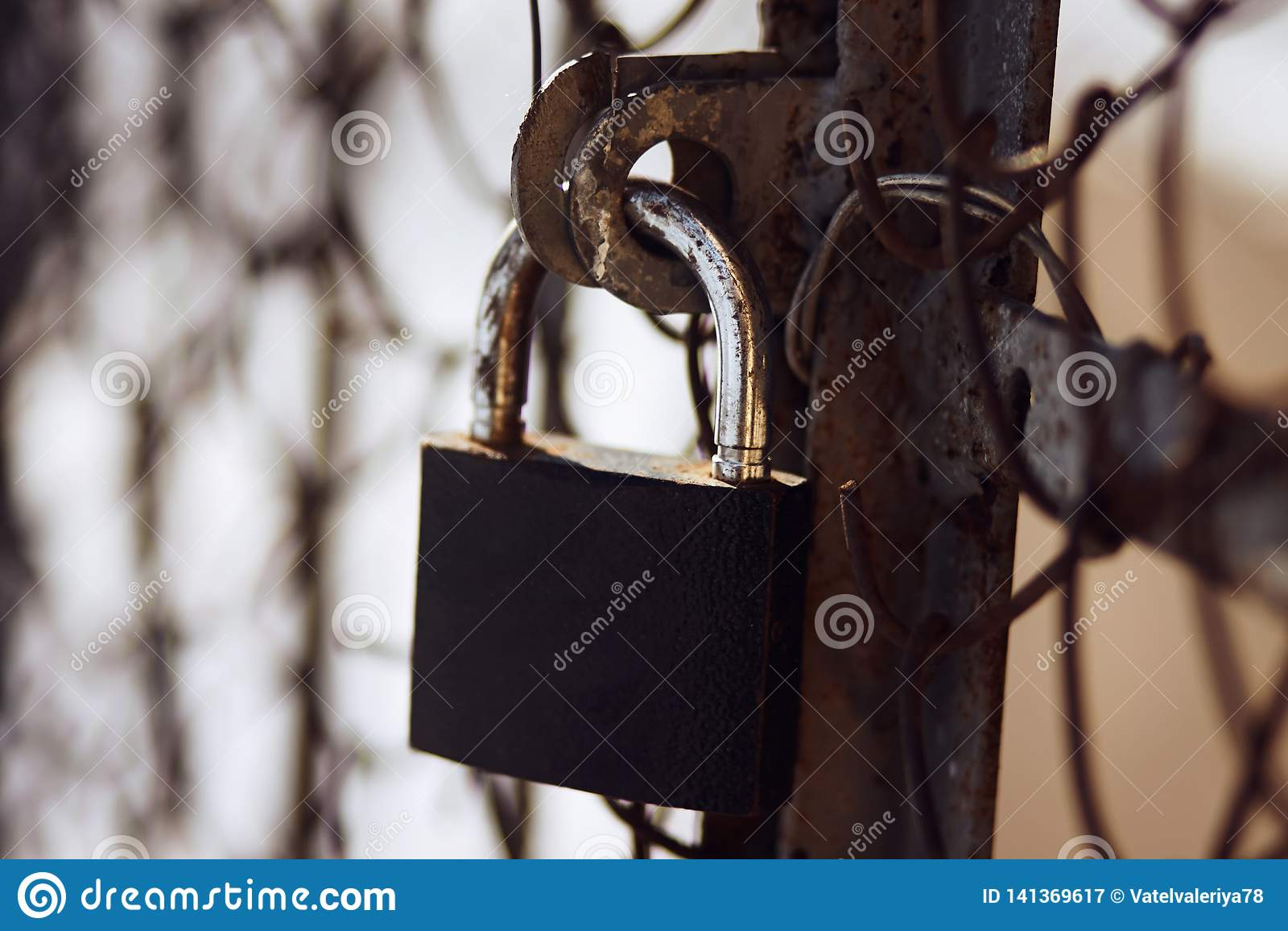 Ржавый затрапезный замок закрывает ржавые старые ворота