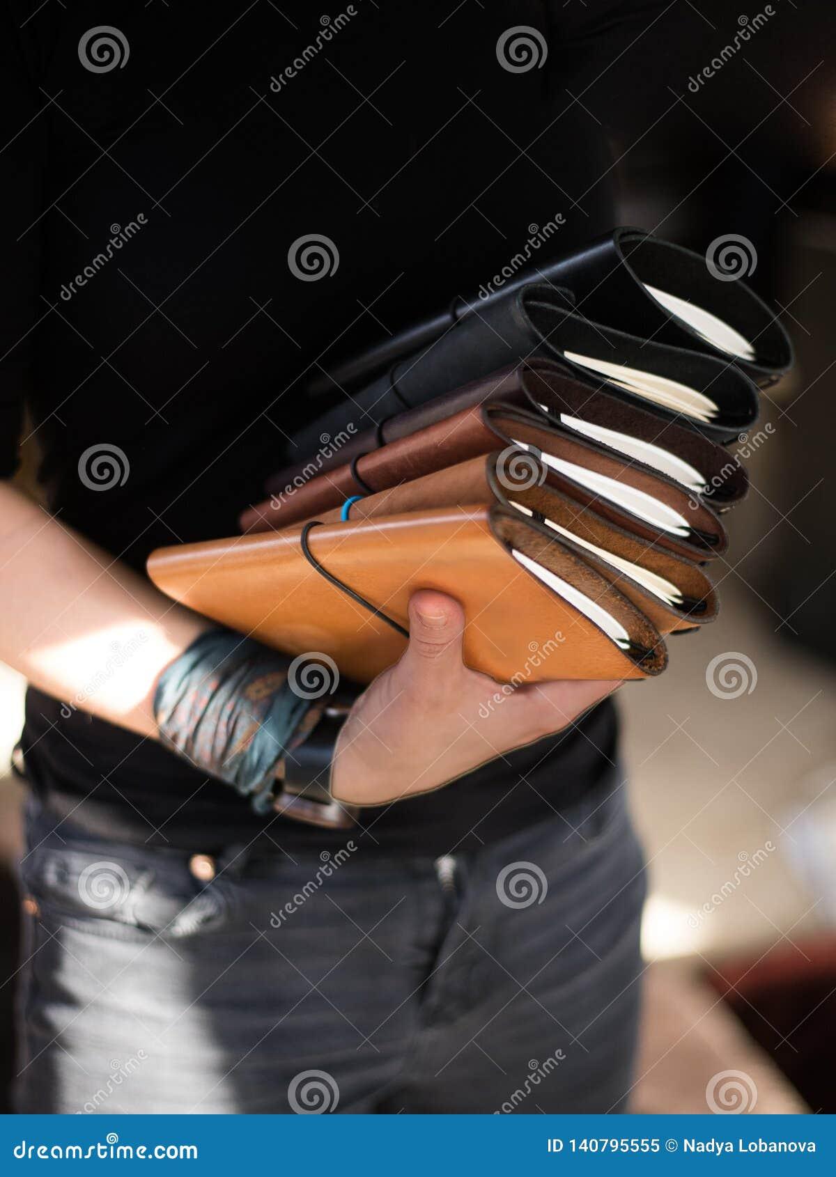 Рука держащ много крышку scetchbook кожаную