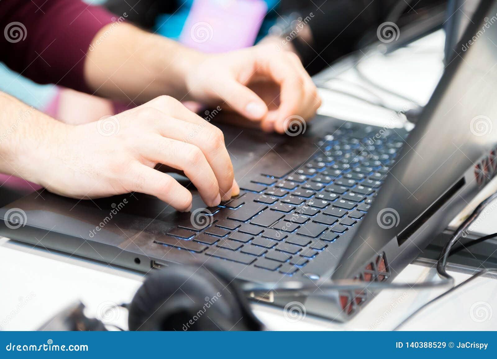 Руки непознаваемого подрезанного молодого человека печатая на ноутбуке