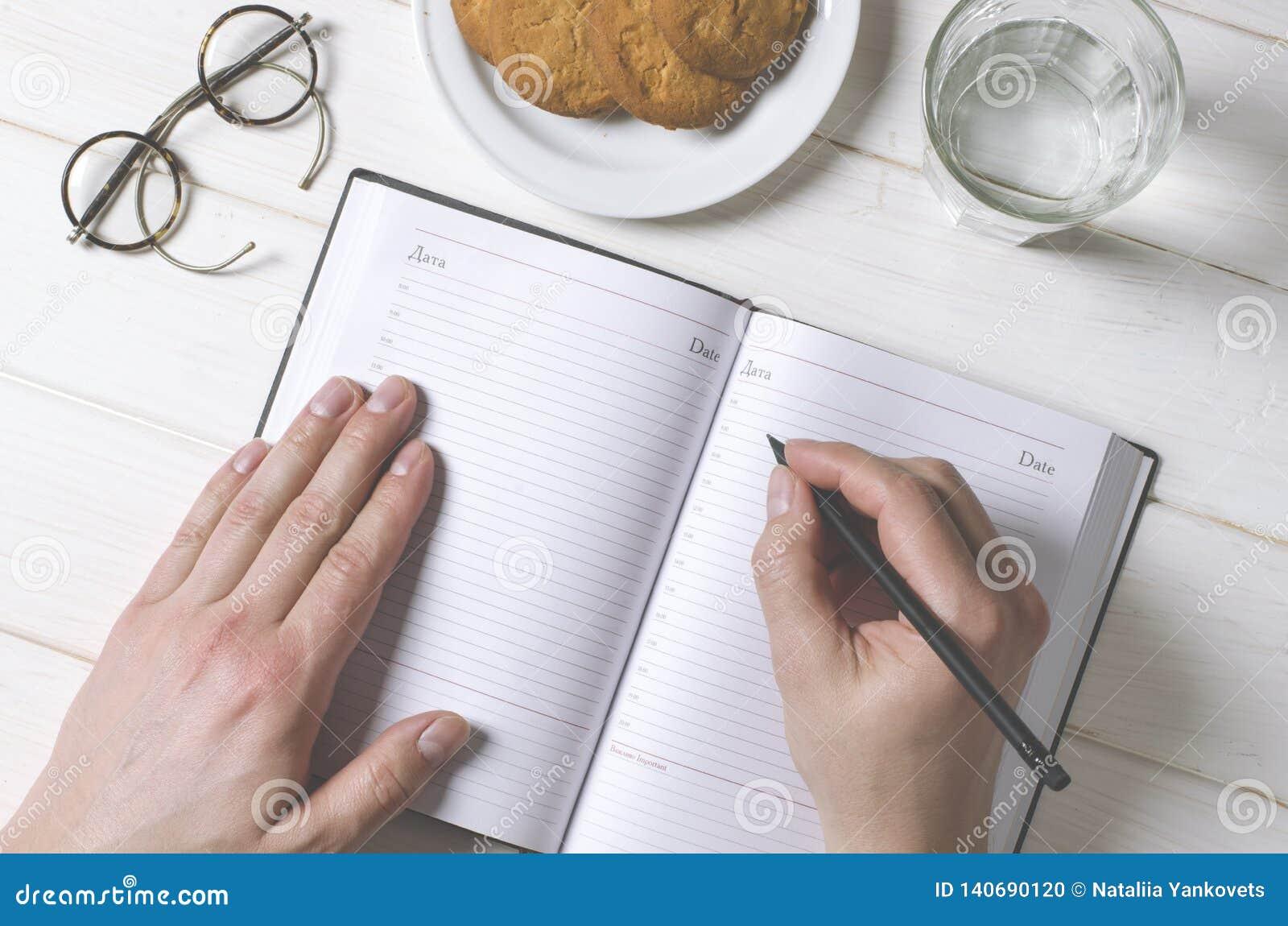 Руки человека писать примечания в тетрадь на деревянном столе в домашнем офисе