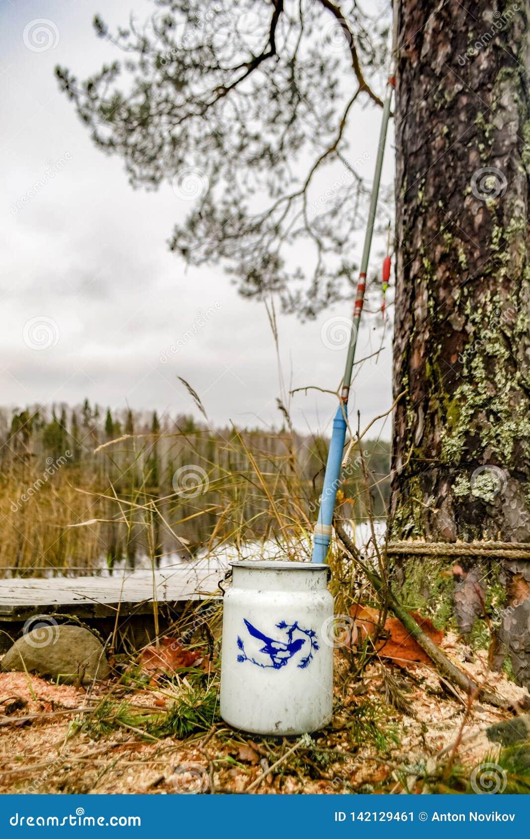 Рыболовная удочка и консервная банка молока на побережье дикого озера