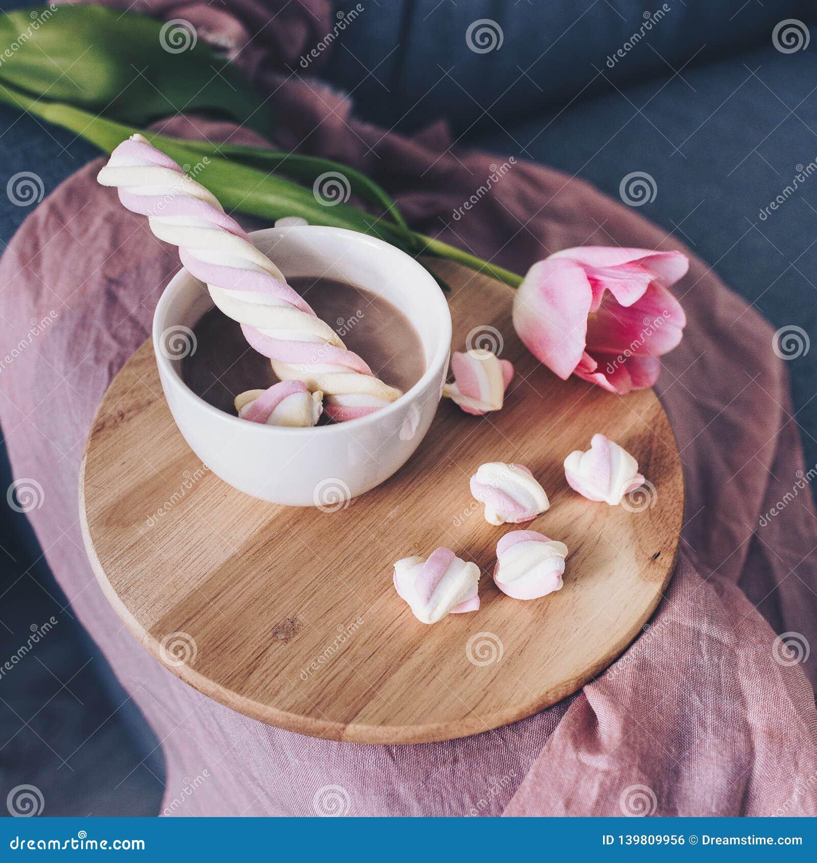 Розовые тюльпаны на серой софе, белая чашка кофе