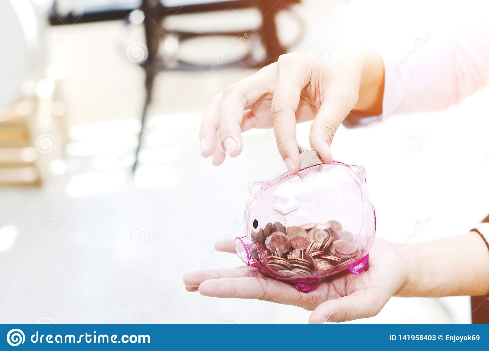 Розовый опарник монетки в руке