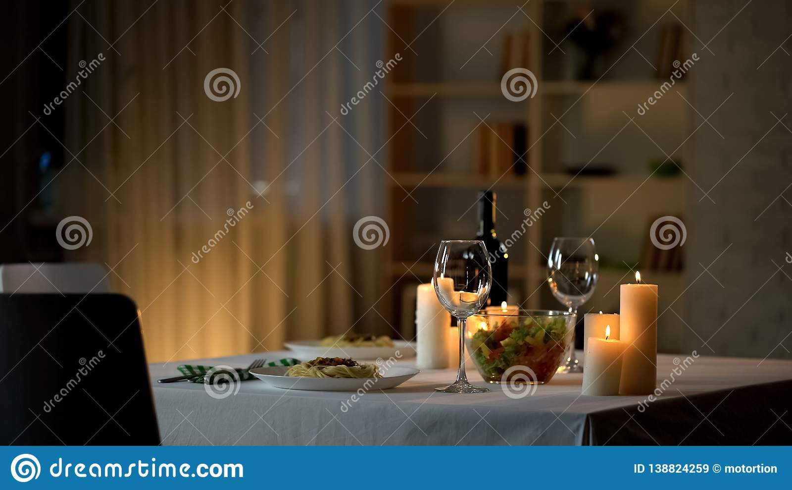 Романтичная сервировка стола обедающего, бокалы и свежий салат в шаре, домашней дате