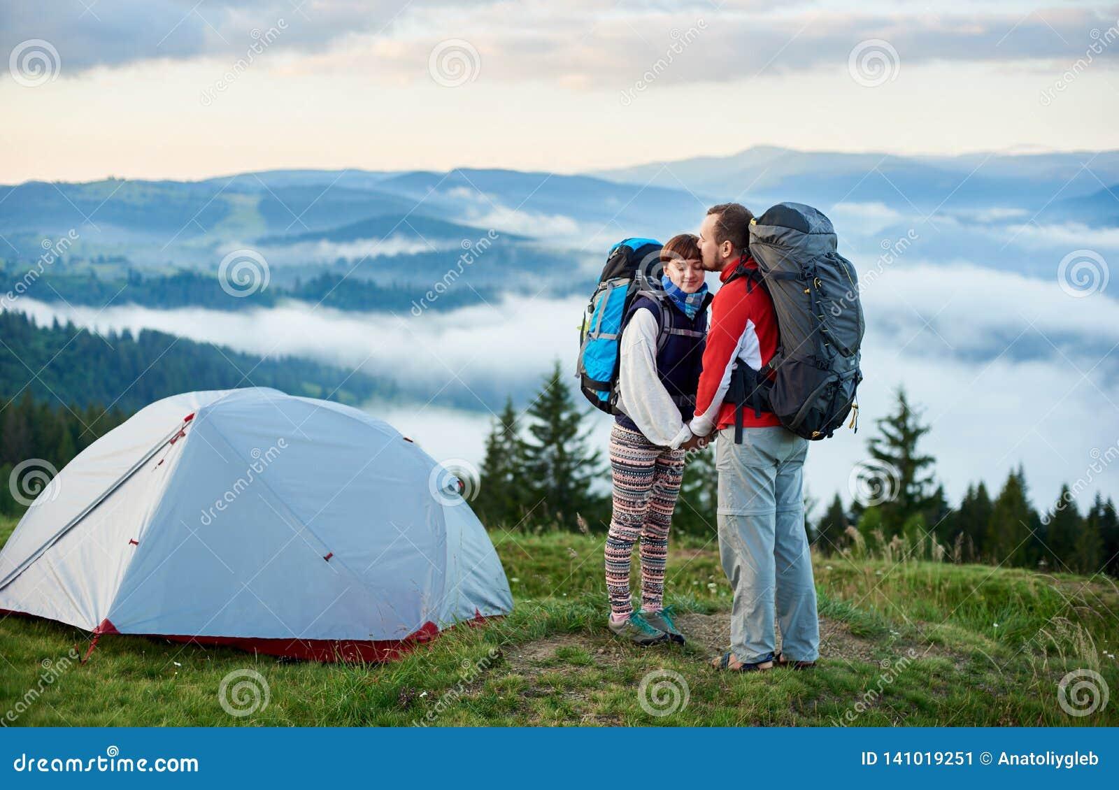 Романтичные пары остатков любовников активных в горах на утре около располагаться лагерем