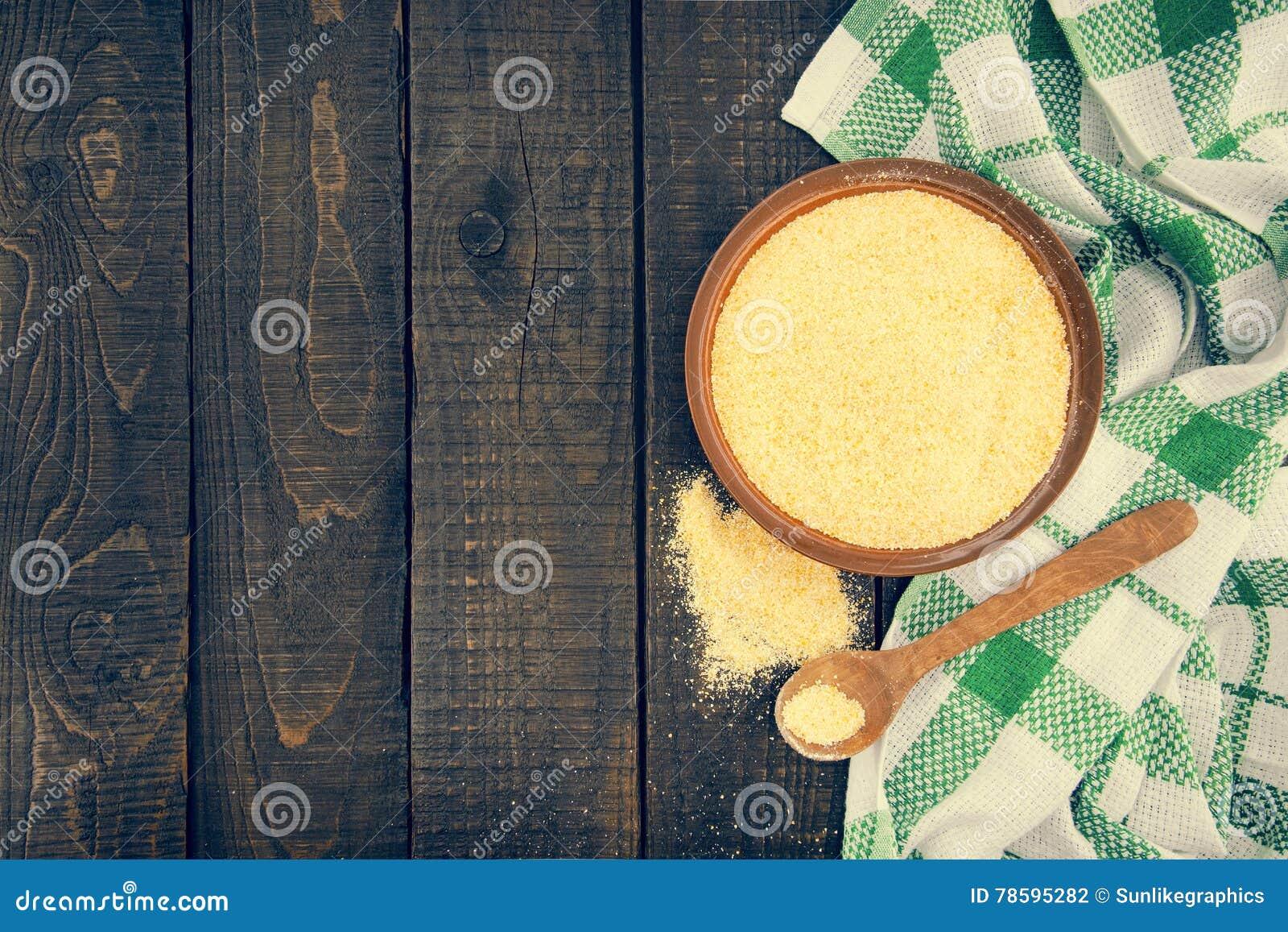 Żółta kukurydzana mąka w ceramicznym pucharze na nieociosanym drewnianym stole Składniki dla przygotowania Włoska tradycyjna pole