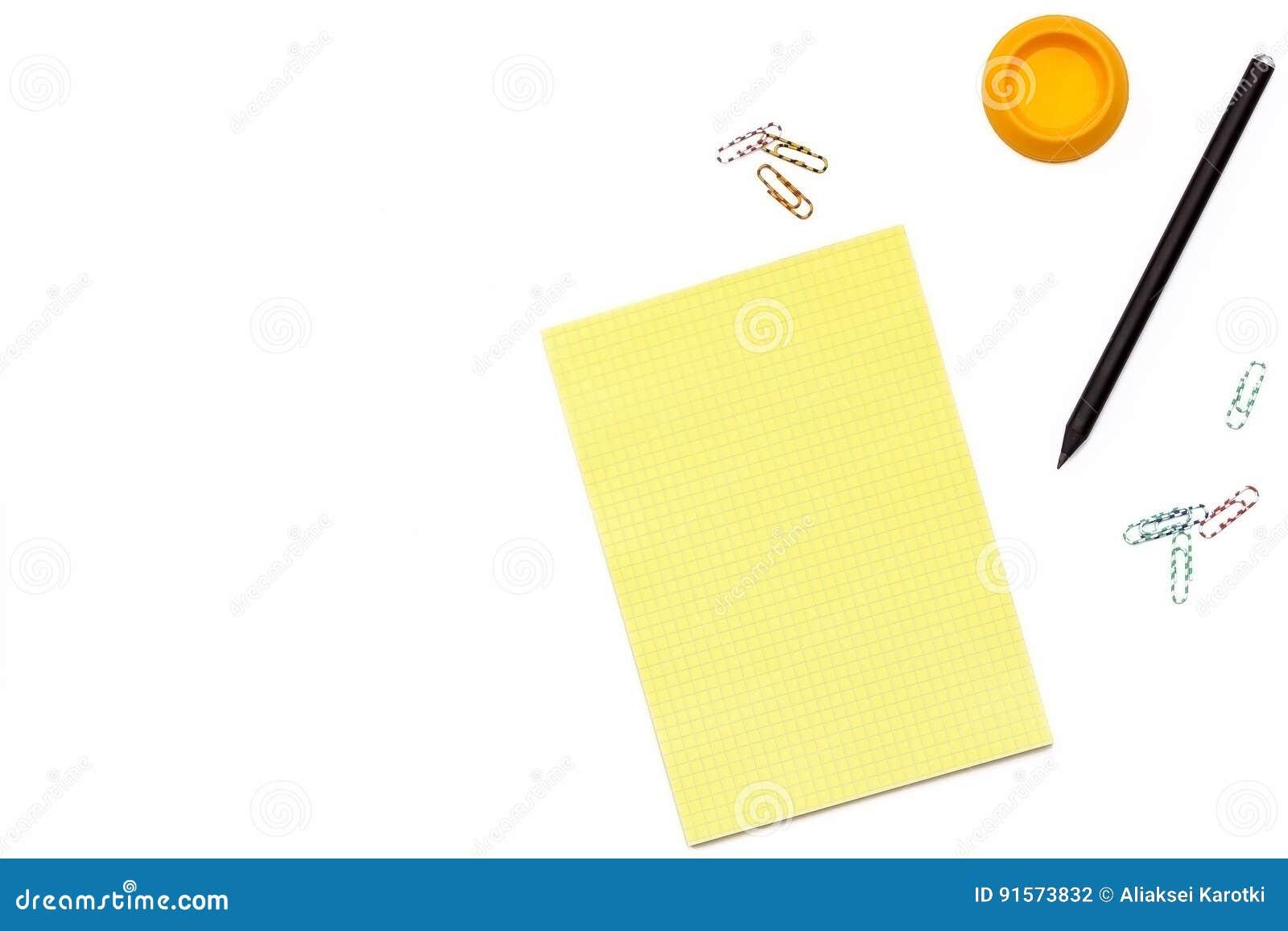 Żółty Notepad, czarny ołówek i papierowa klamerka na białym tle, Minimalny pojęcia miejsce pracy dla biura Mieszkanie nieatutowy