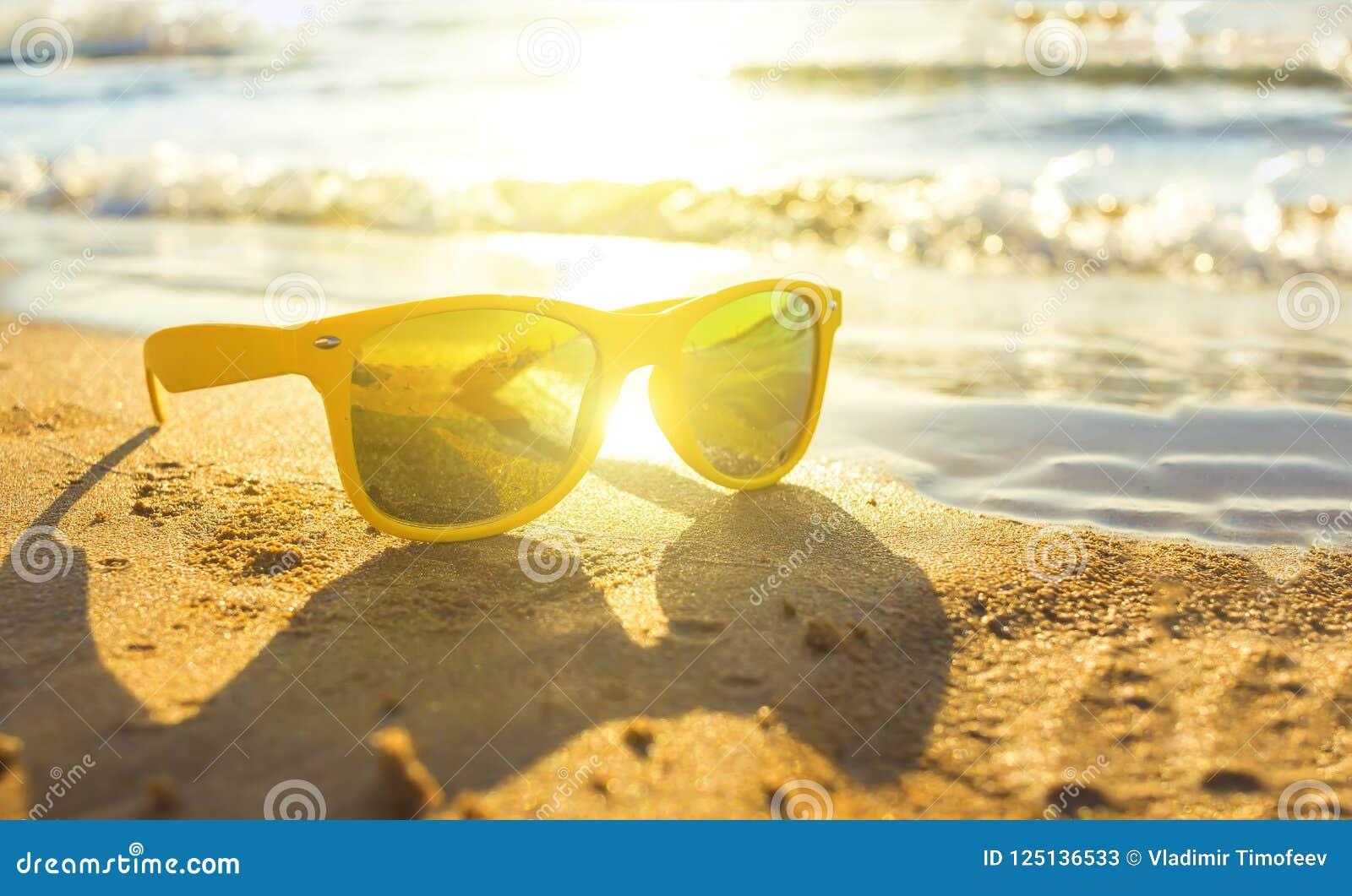 Óculos de sol amarelos à moda pelo mar, areia amarela, sol, profundidade de campo, borrão