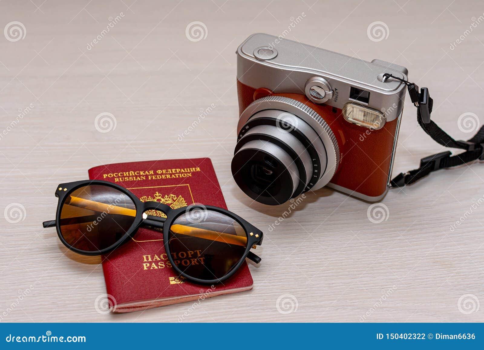 Óculos de sol com o passaporte de um cidadão da Federação Russa e uma câmera imediata da foto em um fundo de madeira branco