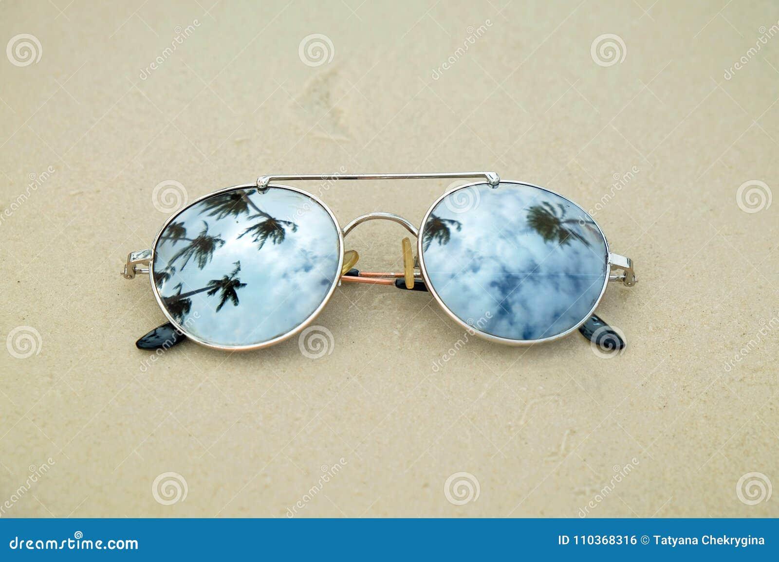 Óculos de sol espelhados perto acima na areia da praia com reflexão das  palmeiras 1d77fe9194