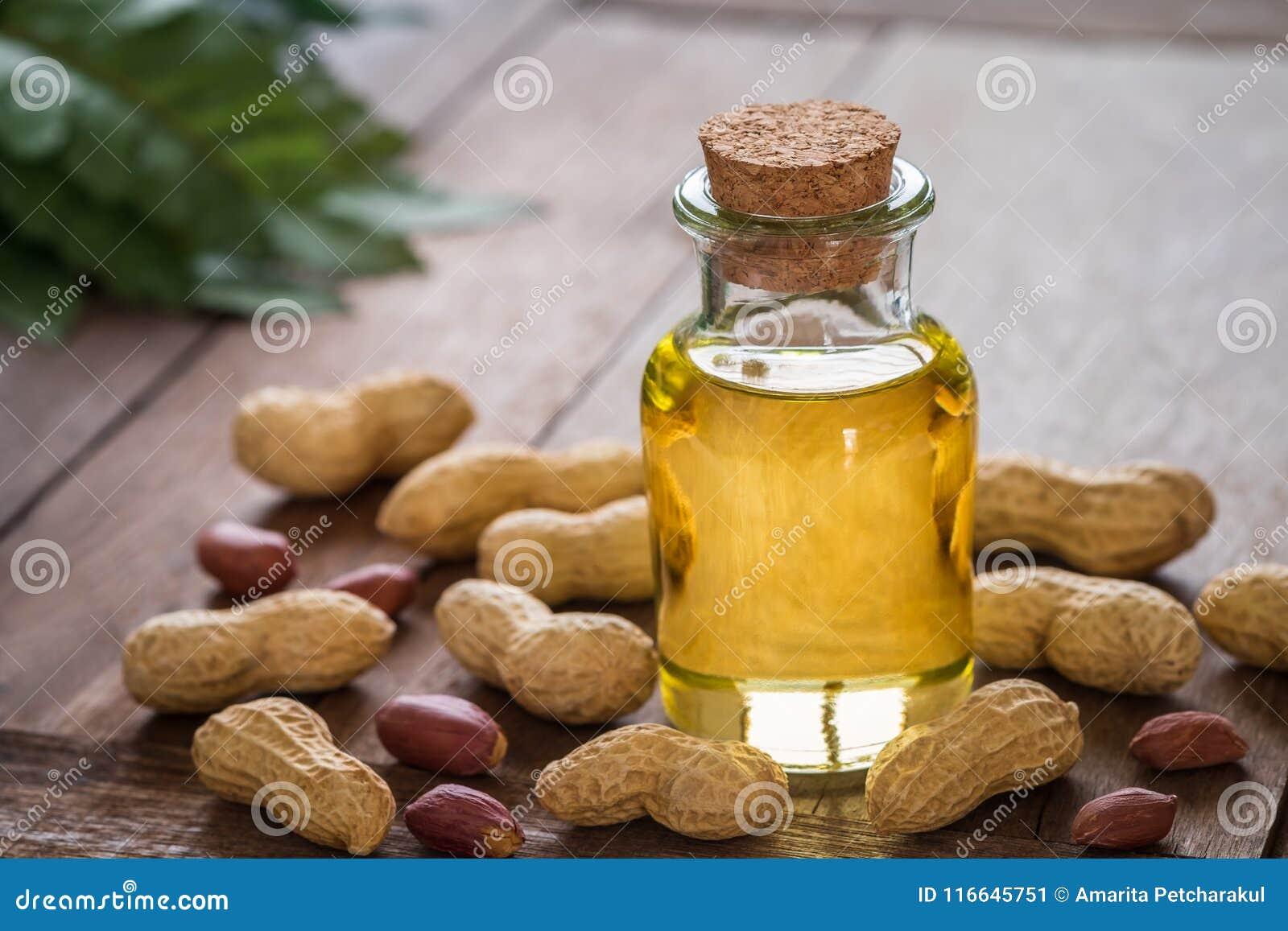 Óleo de amendoim na garrafa de vidro e nos amendoins na tabela de madeira