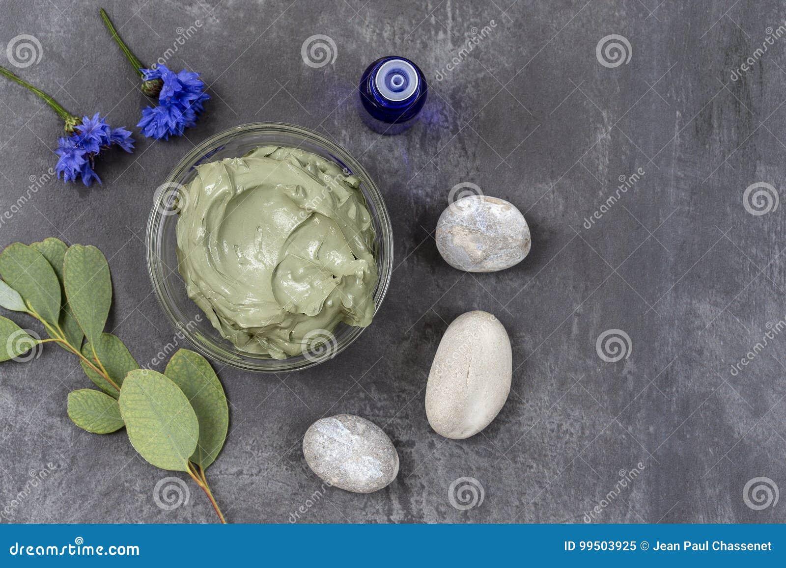 Óleo essencial com argila e a flor cosméticas e ramo do eucalipto, pedras, para tratamentos dos termas, na bacia de vidro no cinz