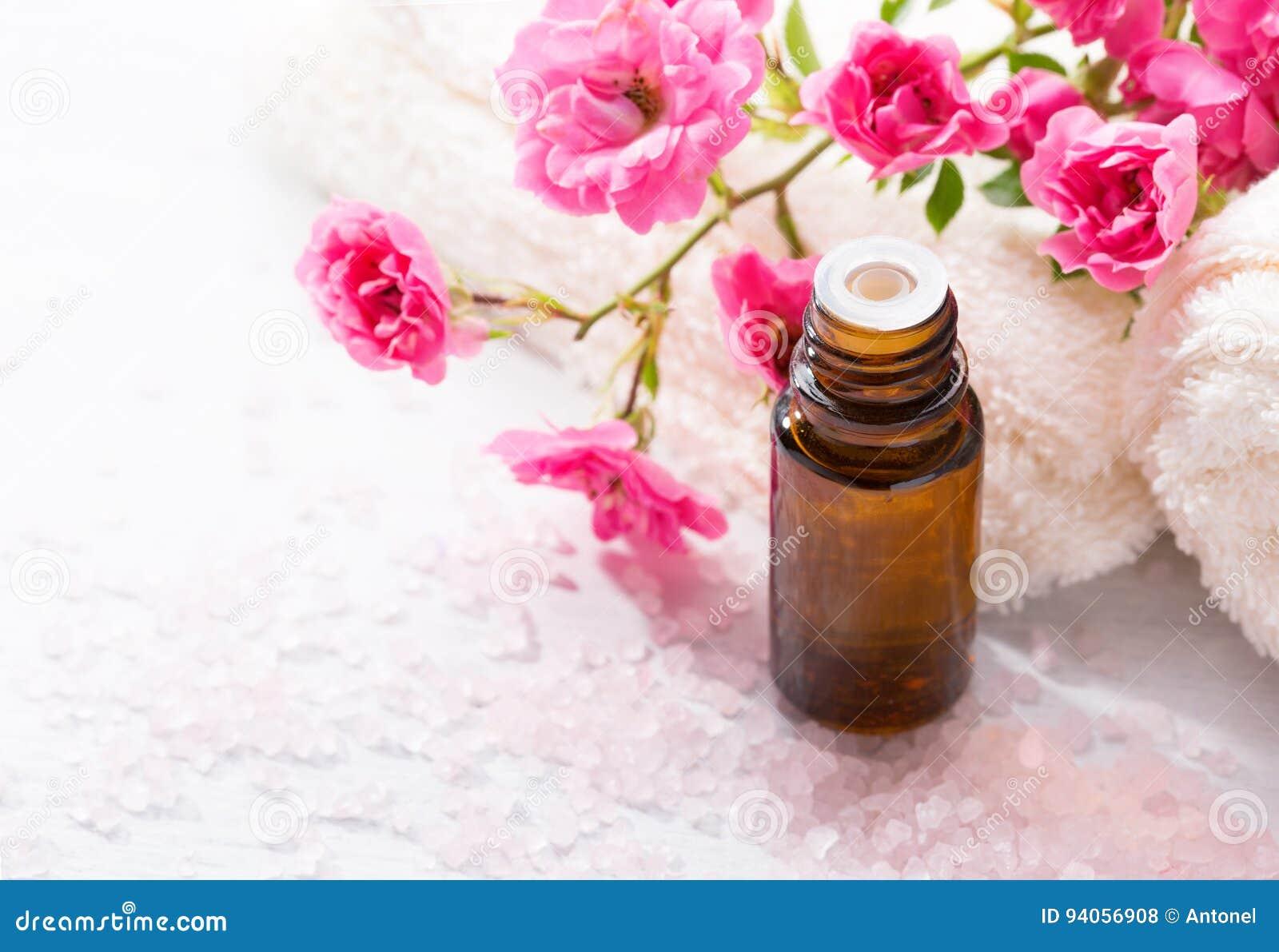 Óleo essencial, sais de banho minerais, ramo da rosa pequena do rosa na tabela de madeira
