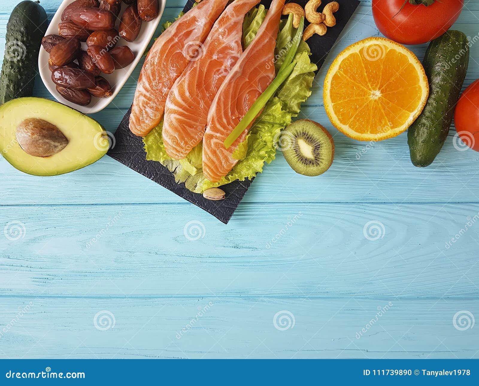 Ômega vermelha 3 dos peixes, variedade nuts em de madeira azul, alimento saudável do jantar fresco do abacate da composição