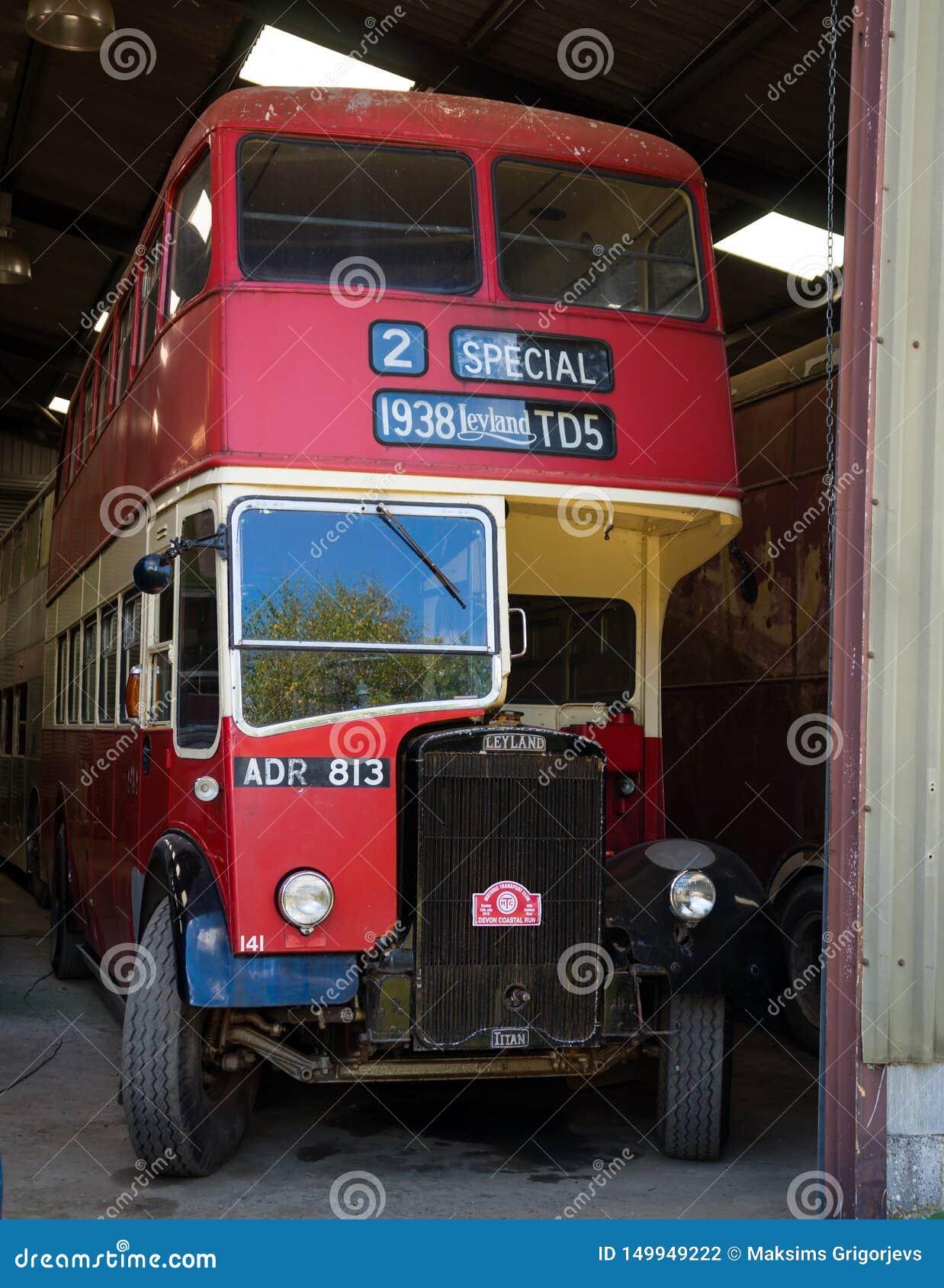 Ônibus de dois andares vermelho do vintage na garagem pronta para a corrida litoral anual de Devon, Winkleigh, Reino Unido, o 5 d
