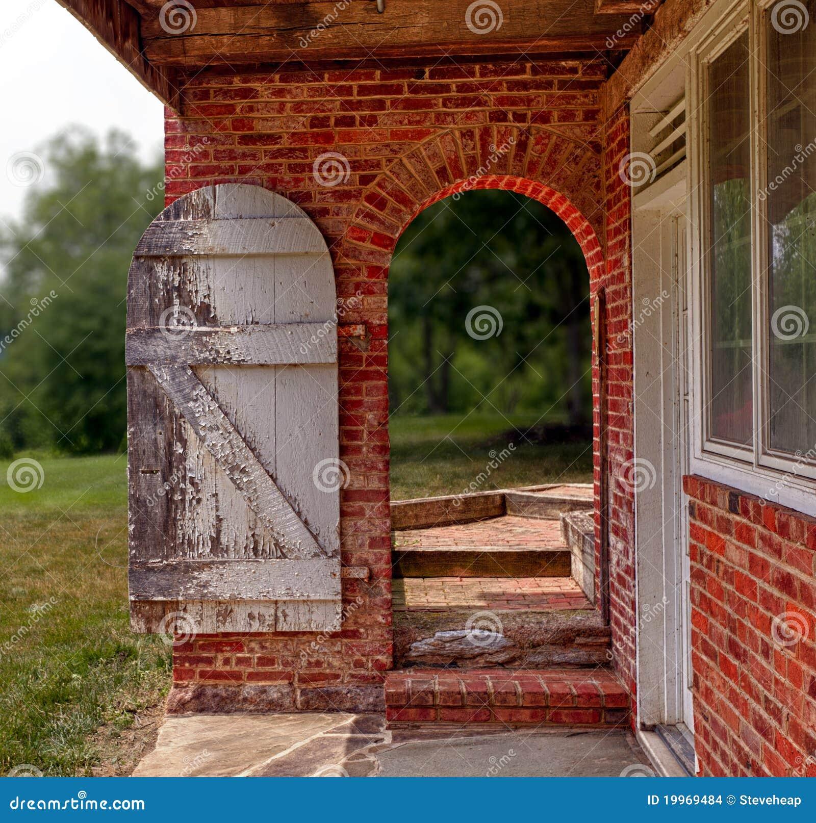 Download Öffnen Sie Hölzerne Tür In Der Backsteinmauer, Um Im Garten Zu  Arbeiten Stockfoto