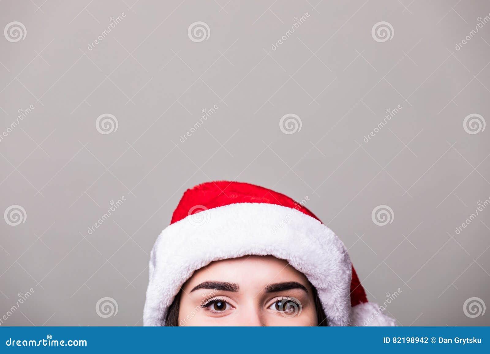 Ögon av flickan i den santa hatten på grå bakgrund