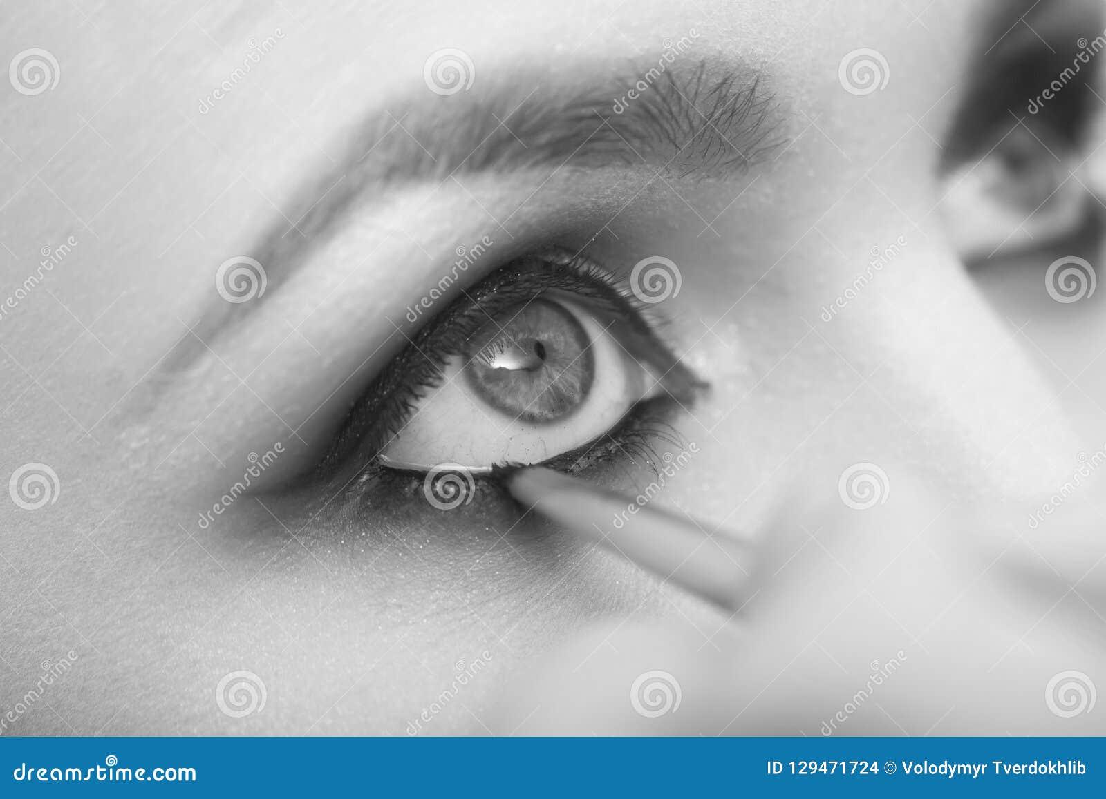 Ögon av flickan som får makeup som drar upp konturerna av med svart skugga