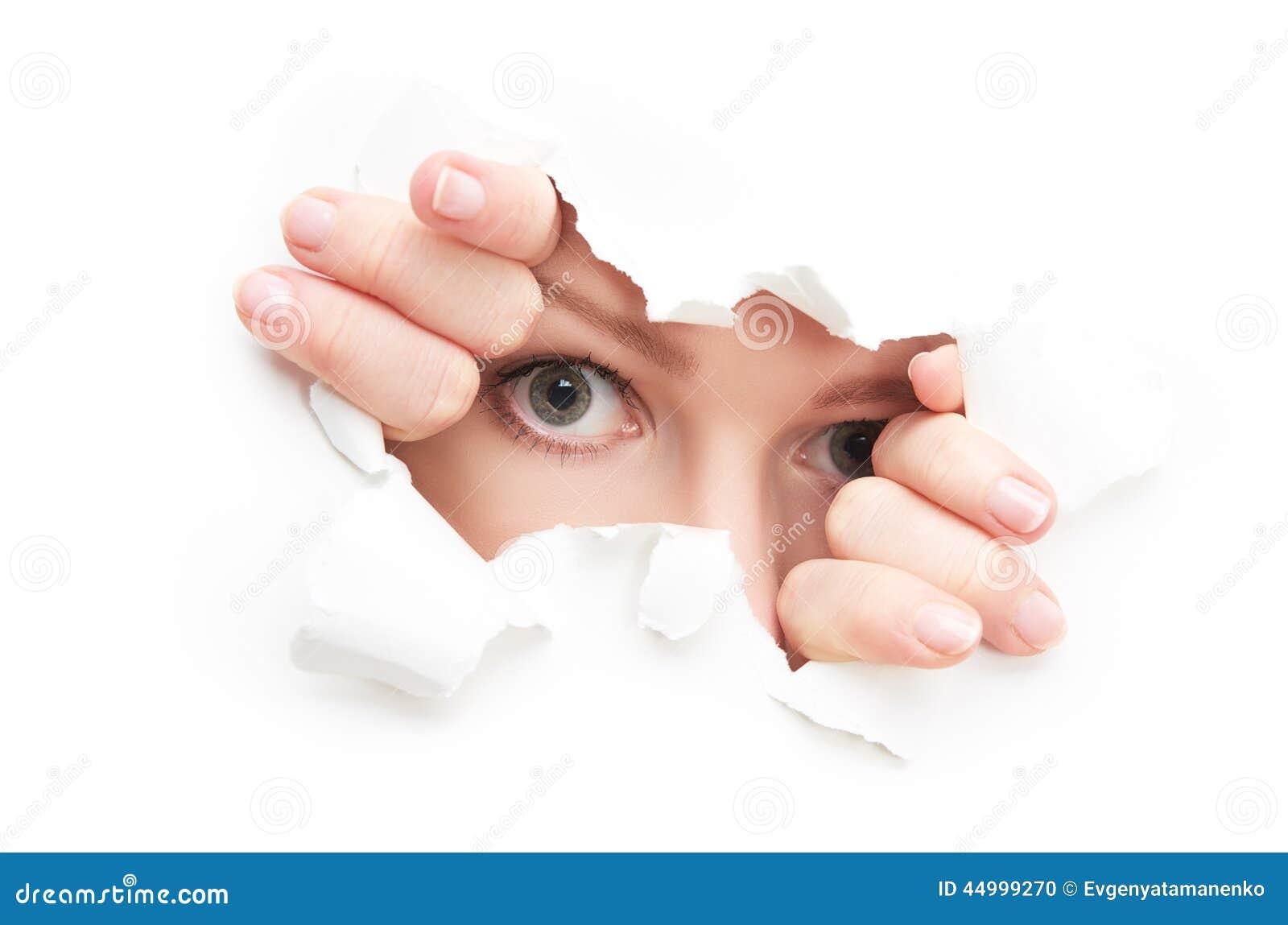 Ögon av kvinnan som kikar till och med ett sönderrivet hål i vitbokaffisch