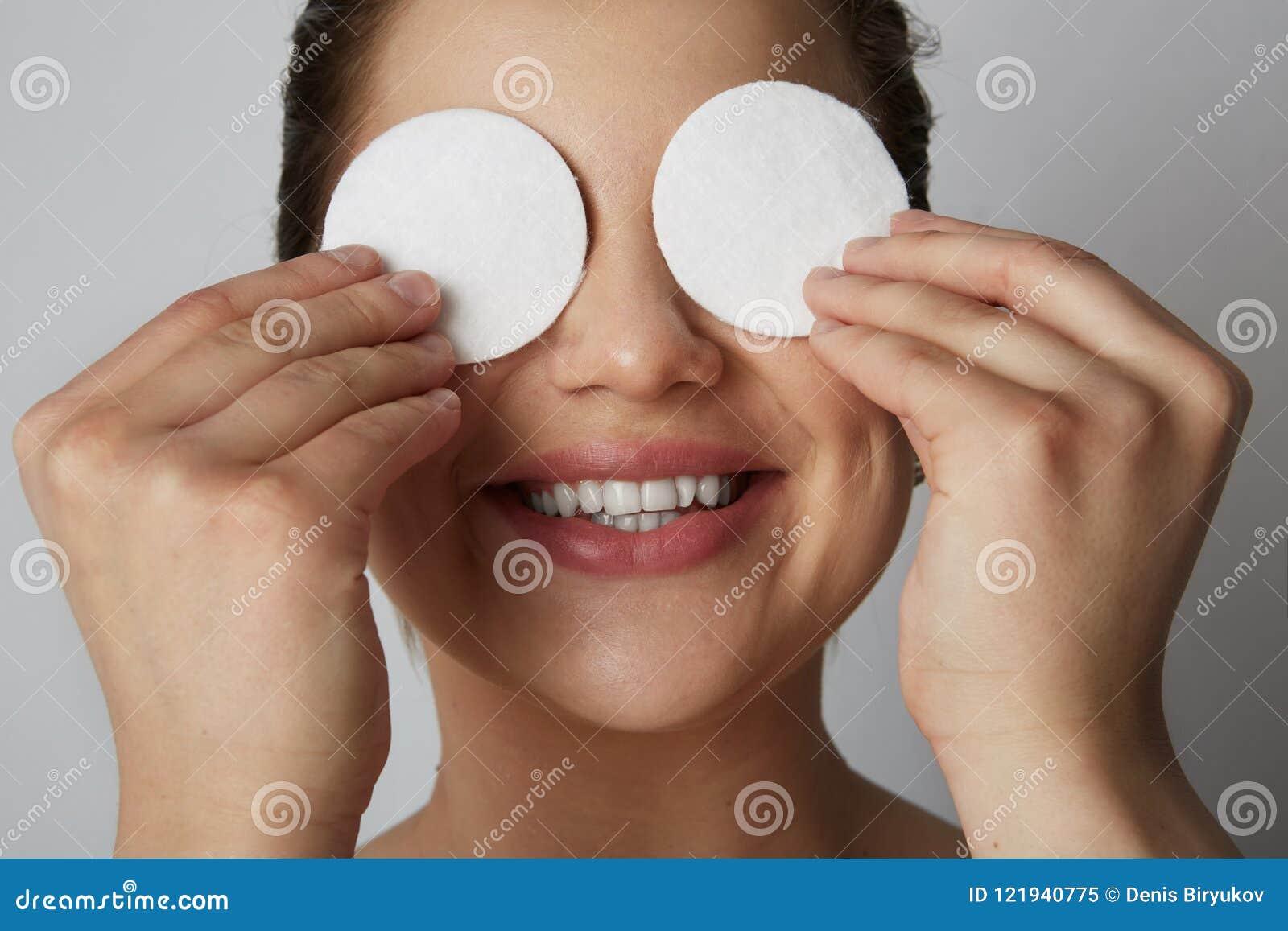 Ögon och framsida för hud för härlig flickamodell uppfriskande med vita bomullsblock över grå studiobakgrund Modell med ljus